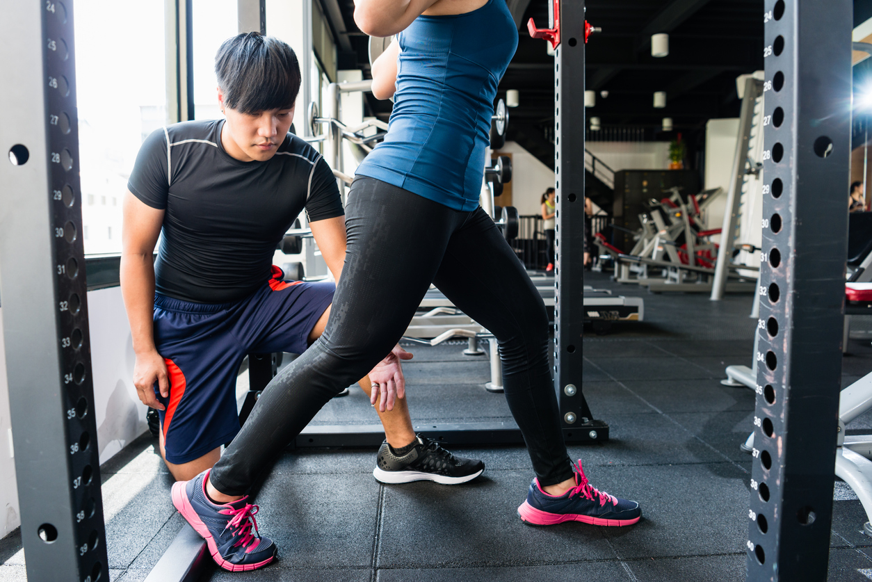 personal trainer is teaching squat to woman